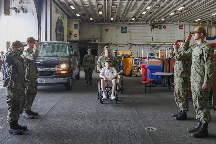 A man in a wheelchair is pushed forward. To his left and right, service members dressed in military uniforms salute.