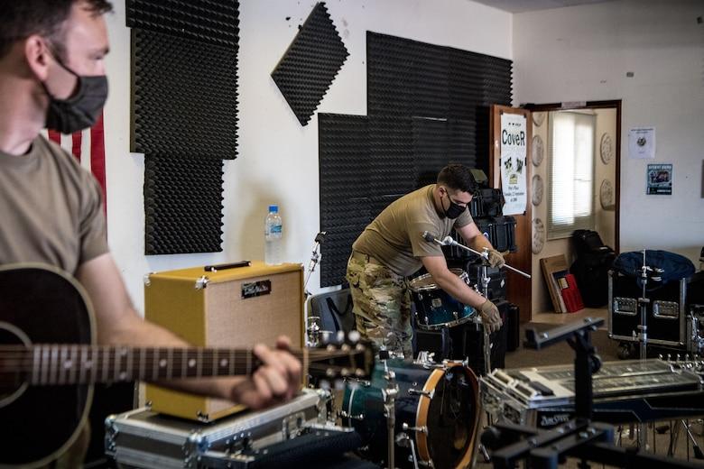 man sets up drum kit