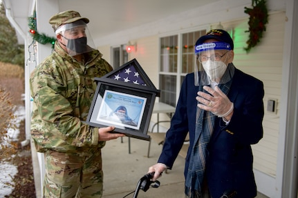 Col. Adam Rice (left), vice wing commander of the 158th Fighter Wing, Vermont Air National Guard, presents a flag flown in the F-35A Lightning II to WWII veteran Lenny Roberge, Vermont's oldest living veteran, outside his nursing home in South Burlington, Vt., Dec. 22, 2020. In order to honor Roberge, Airmen from the 158th Fighter Wing had a flag flown in an F-35 during a combat training sortie over the mountains of Vermont and New York. (U.S. Air National Guard photo by Senior Master Sgt. Michael Davis)
