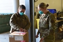 Staff Sgt. Michelle Krous, 341st Healthcare Operations Squadron noncommissioned officer in charge of acquisitions, opens a box of delivered COVID-19 vaccines, Dec. 30, 2020, at Malmstrom Air Force Base, Mont.