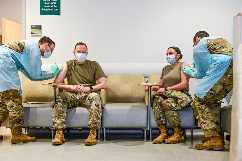 Two soldiers sit with their sleeves rolled up as two other service members administer shots to them.