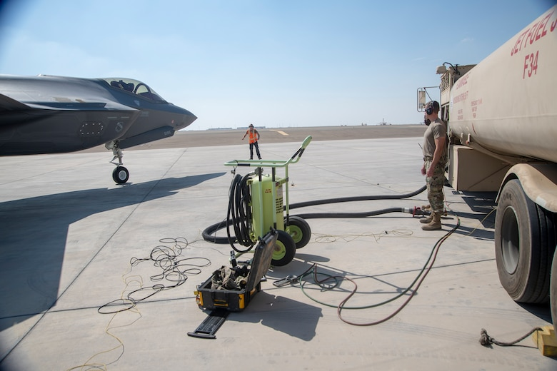 Members of the 380th Expeditionary Aircraft Maintenance and Logistics Readiness Squadrons standby as an F-35A Lightning II taxis toward a hot pit refueling point on the Al Dhafra Air Base flightline, United Arab Emirates, Jan. 29, 2020 . A hot pit refueling is the process in which ground crew Airmen refuel an aircraft while its engines are still running, minimizing the time required to get the aircraft airborne again. This capability enhances the readiness of the wing and ability to execute the air tasking order. (U.S. Air Force photo by Staff Sgt. Anna-kay Ellis)