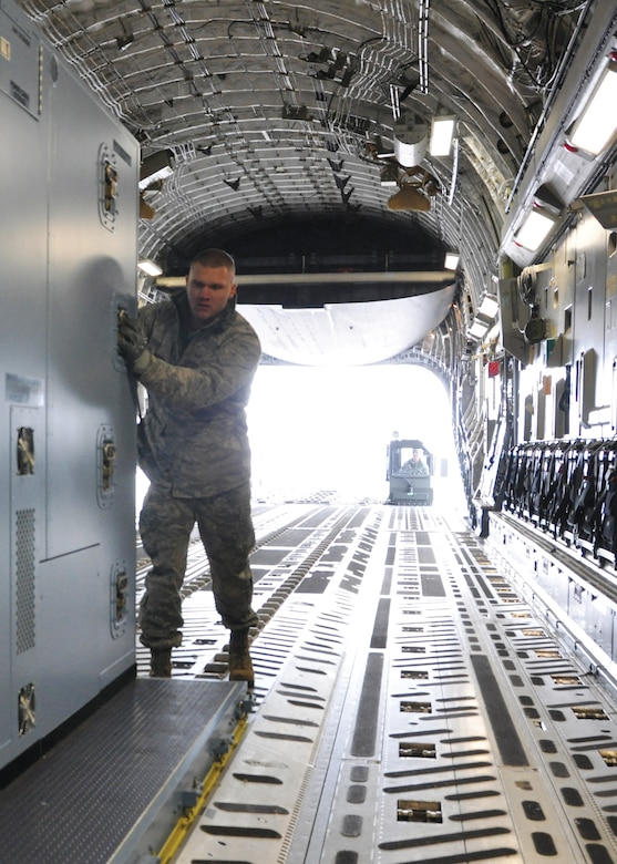 Staff Sgt. Dakota Coniglio, ramp operations specialist with the 87th Aerial Port Squadron, pushes an air transportable galley-lavatory onto a C-17 Globemaster III at Wright-Patterson Air Force Base, Ohio. The ramp operations duty section works closely with the load planning duty section, both part of the aerial port squadron, to safely and quickly airlift cargo and people in support of the Air Force mission. (U.S. Air Force photo/1st Lt. Rachel Ingram)