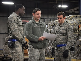 Tech Sgt. Taylor Shaw, load planner with the 87th Aerial Port Squadron, reviews a load plan with Senior Airmen Jason Turner and Gabriel Clark, both ramp operations specialists with the 87th APS.  The load plan is an essential tool in making cargo is balanced, safe and air-worthy before for any C-17 Globemaster III flight.  (U.S. Air Force photo by Senior Airman Angela Shay)