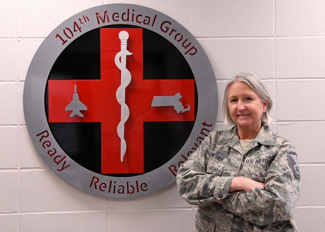 U.S. Air Force Master Sgt. Terrylee Lois Crowther, a dental technician assigned to the 104th Fighter Wing, Massachusetts Air National Guard, poses for a photo in front of the 104th Medical Group crest at Barnes Air National Guard Base, Mass., Feb. 2, 2020. Crowther is the NCOIC of dental at the 104th FW and is nearing her retirement after 40 years of military service. (U.S. Air National Guard photo by Airman Camille Lienau)