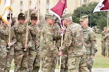 """Cmd. Sgt. Maj. Clark J. Charpentier (left) the incoming Command Sergeant Major, accepts the unit colors from Maj. Gen. Dennis P. LeMaster, commander, U.S. Army Medical Center of Excellence, as Cmd. Sgt. Maj. William """"Buck"""" O'Neal looks on. (Photo Credit: Jose Rodriguez, Public Affairs, MEDCoE)"""