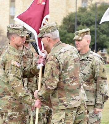 "Command Sgt. Maj. Clark J. Charpentier (left) the incoming U.S. Army Medical Center of Excellence Command Sergeant Major, accepts the unit colors from Maj. Gen. Dennis P. LeMaster, MEDCoe commander, as Command Sgt. Maj. William ""Buck"" O'Neal looks at the MacArthur Parade Field at Joint Base San Antonio-Fort Sam Houston Jan. 31."