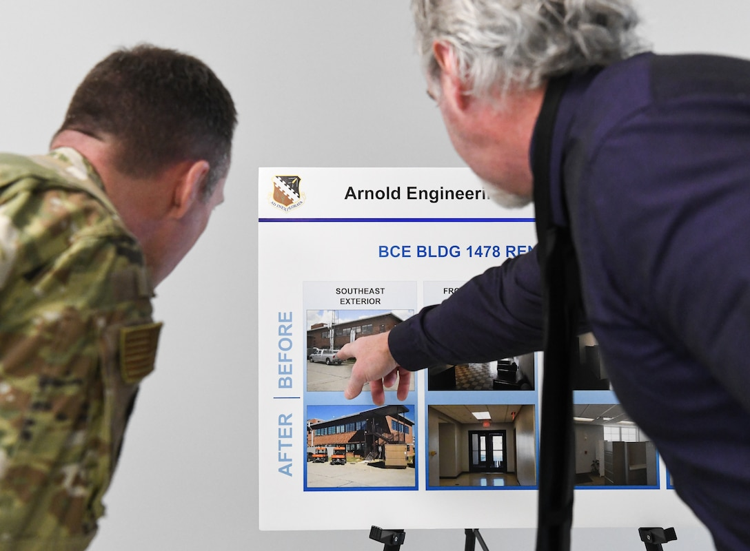"Air Force project manager Tony Pennington, right, points out an issue with the Civil Engineering, Operations and Maintenance Building evident in a ""before"" photo during a ribbon cutting celebrating the renovation of the building at Arnold Air Force Base, Tenn., Jan. 6. Also pictured is Col. Charles Roberts, Test Support Division chief. (U.S. Air Force photo by Jill Pickett)"