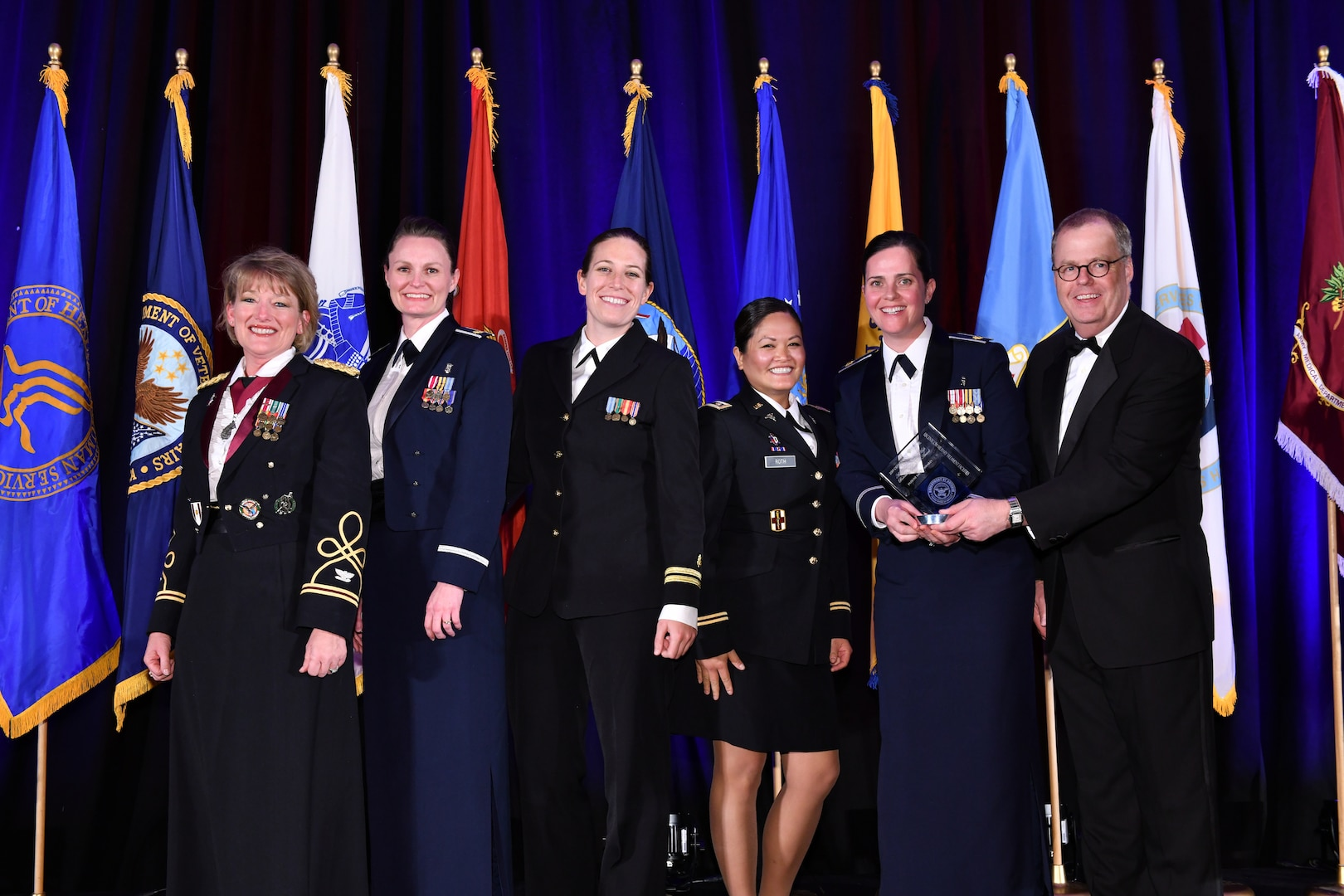 U.S. Central Command's (USCENTCOM) clinical operations team poses for a group photo during an awards ceremony at the annual meeting of AMSUS, the Society of Federal Health Professionals, Dec. 5 2019. From left to right; U.S. Army Col. Tamara Funari, USCENTCOM's Chief of Clinical Operations; U.S. Air Force Maj. Steffanie Solberg, U.S. Air Force Central Command's Chief of Clinical Operations; U.S. Navy Lt. Ashley Hanhurst, Navy Nurse Corps, Walter Reed National Military Medical Center; U.S. Army Cpt. Amanda Roth, microbiologist at US Army Medical Research Directorate – Africa; U.S. Air Force Maj Alice Barsoumian, infectious disease physician at San Antonio Military Medical Center; Thomas McCaffery, Assistant Secretary of Defense for Health Affairs. (Courtesy photo provided by Eddie Arrossi/ AMSUS)