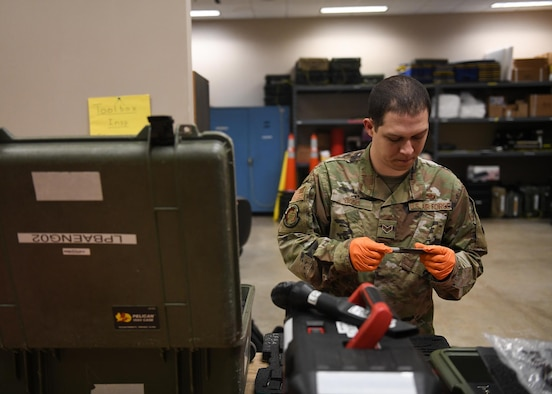 An Airman inspects a small tool.