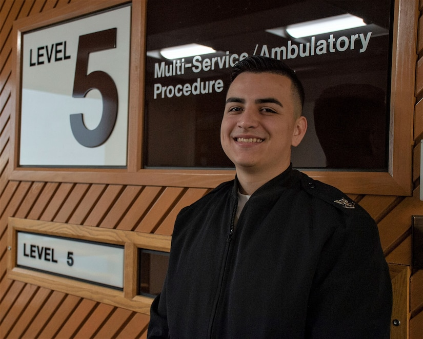 A sailor stands in front of a hospital unit sign in a hallway, smiling for the camera.