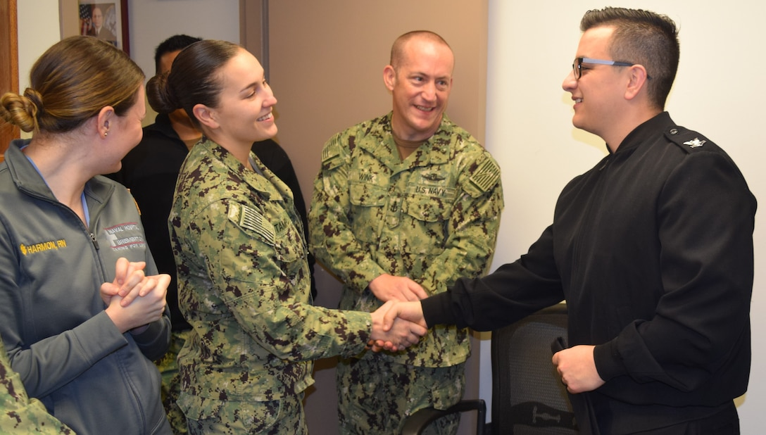 A sailor in a black jacket shakes the hand of another sailor in a Navy working uniform. Three other sailors stand around them smiling.