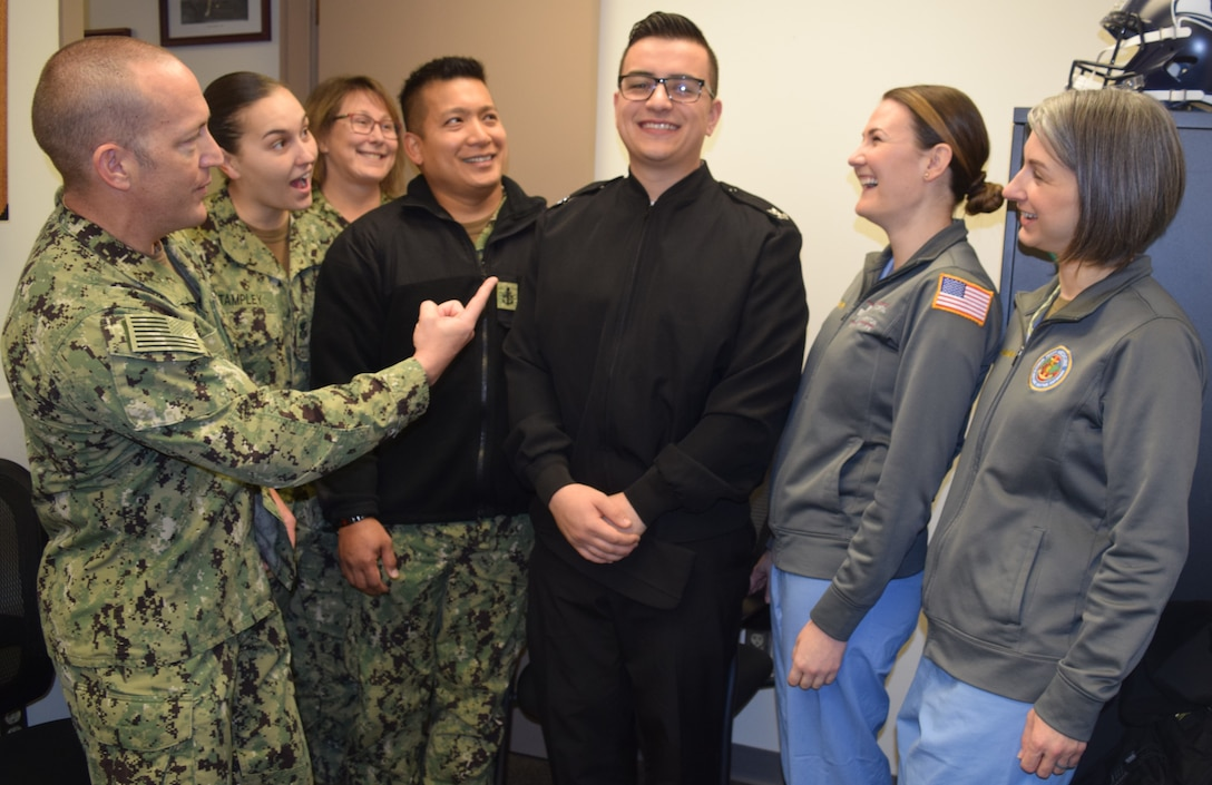Seven Navy sailors laugh together in an office. One points toward the man in the middle.