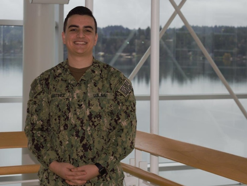 A sailor in his Navy working uniform poses for a photo by a window that overlooks a river.