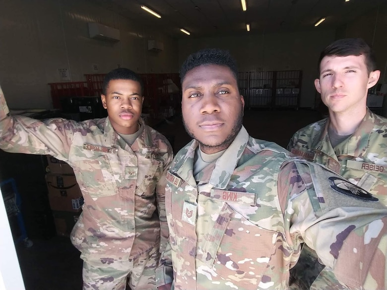 From left to right, U.S. Air Force Senior Airman TeDera Graves II, Tech. Sgt. Alton King and Staff. Sgt. Nolan Geiser, post office clerks deployed to an undisclosed location, take a photo in their work area Sept. 21, 2018. While deployed, Graves made improvements to two processes which were later implemented across the Department of Defense and the U.S. Air Force Central Command area of responsibility. (Courtesy photo)