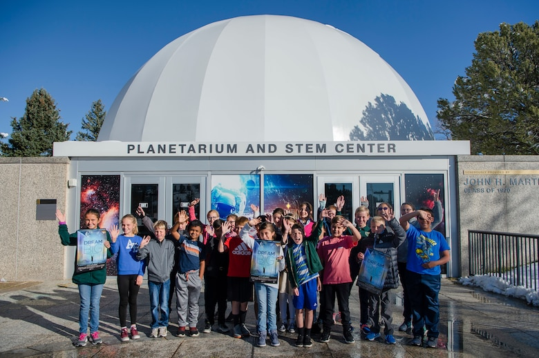 """Students from St. Paul Catholic School in Colorado Springs wave for the camera following the planetarium's """"Dream Big: Engineering our World"""" show at the Air Force Academy, Colo., Oct. 25, 2019. The school's STEM teacher said the experience was incredible and inspiring and the new multimedia capabilities of the planetarium captivated him and the students. (U.S. Air Force photo by Trang Le)"""