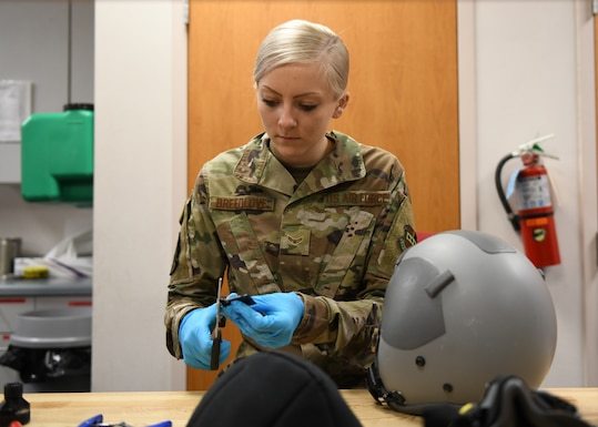 Airman 1st Class Maggie Breedlove, 9th Operations Support aircrew flight equipment specialist, measures and cuts Velcro pieces that will be placed in the inside of a flyers lightweight helmet, Jan. 22, 2020 at Beale Air Force Base, California. These pieces of Velcro will attach an energy absorbing liner to the helmet. The purpose of an energy absorbing liner is to reduce impact energy to the head of a pilot. (U.S. Air Force photo by Airman 1st Class Luis A. Ruiz-Vazquez)
