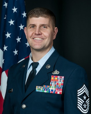 Official portrait of Command Chief Tory Taylor, wearing blues with flag in the background