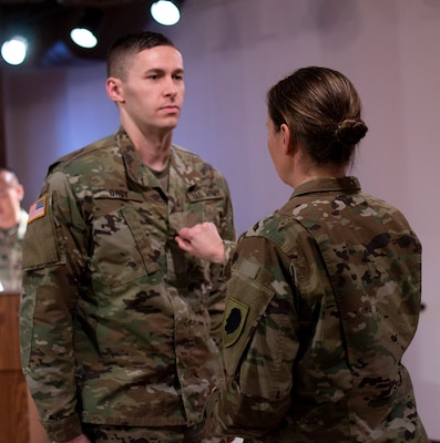 Sgt. 1st Class Larry Groy's sister, Sgt. Maj. Mary Groy, places his new rank on his uniform during the promotion ceremony Jan. 31 at the Illinois State Military Museum.