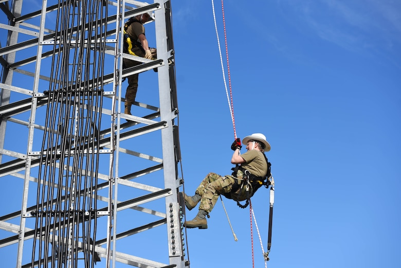 Chief Master Sgt. Kellie Brisse (right), 14th Operations Group superintendent, propels down a radio tower supervised by Senior Airman Brandon Culp, 14th Operations Support Squadron's Radar, Airfield and Weather Systems journeyman, at the Ground-To-Air Transmitter and Receiver Site Jan. 28, 2020, on Columbus Air Force Base Mississippi. Training is implemented to help Airmen become familiar and comfortable with the equipment they use, and create safe work habits. (U.S. Air Force photo by Airman 1st Class Jake Jacobsen)