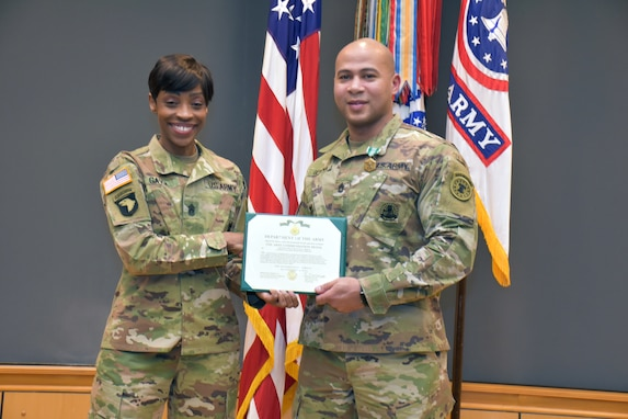 Female Soldier in green camouflage uniform holds green folder with white certificate with male Soldier in green camouflage uniform in front of the U.S. flag and the Army and Recruiting Command colors all of which are red, white and blue.