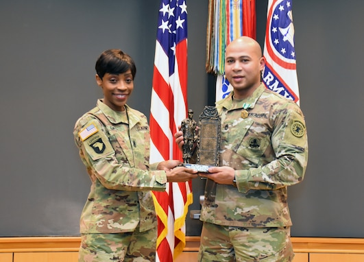 Female Soldier in green camouflage uniform holds bronze and black Soldier statue with male Soldier in green camouflage uniform in front of the U.S. flag and the Army and Recruiting Command colors all of which are red, white and blue.