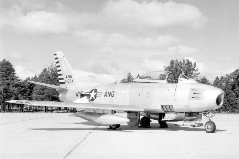A F-86A Sabre fighter jet sits on an air strip as trees can be seen in the background.
