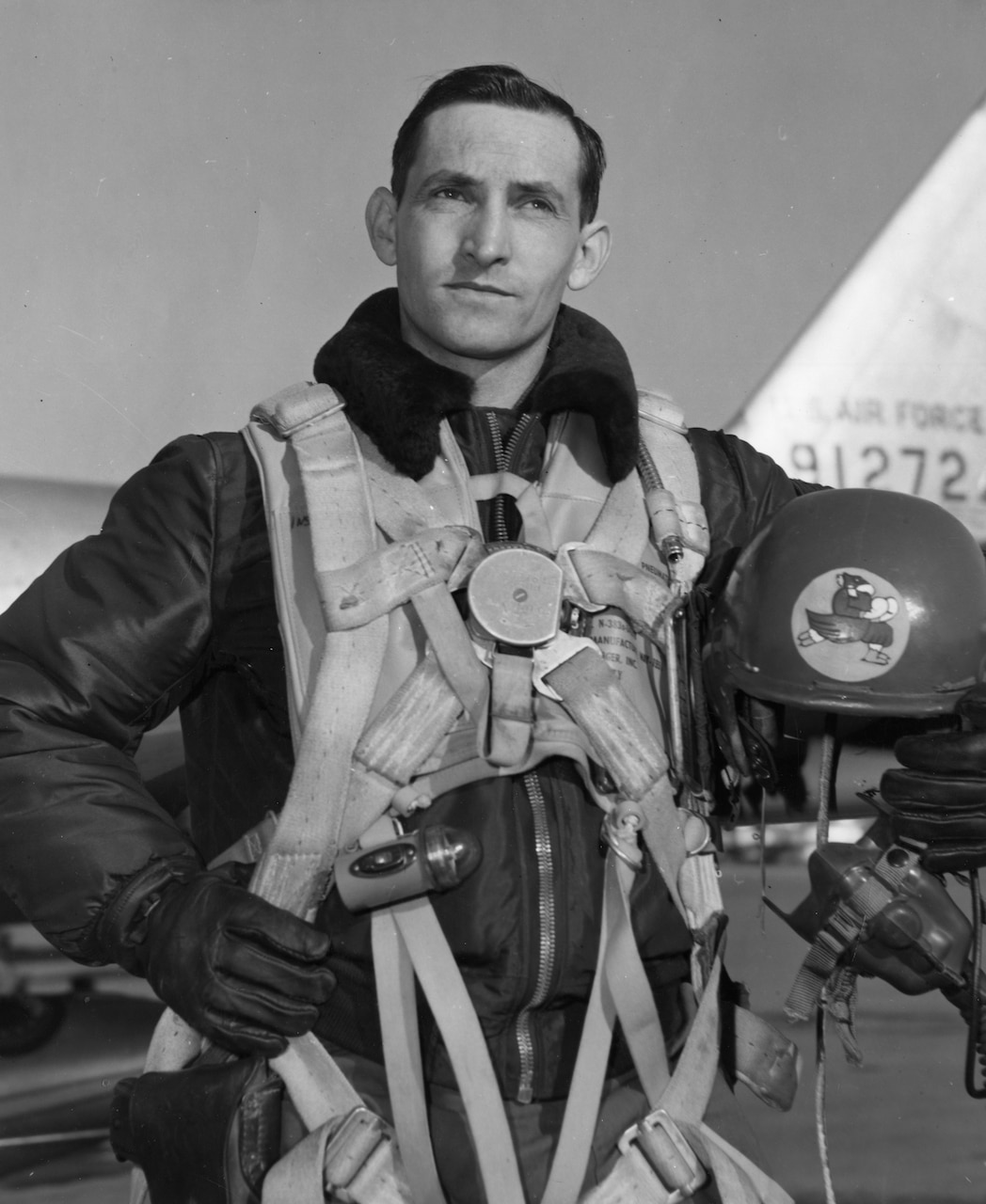 A pilot holds his parachute gear in one hand and his helmet in the other.