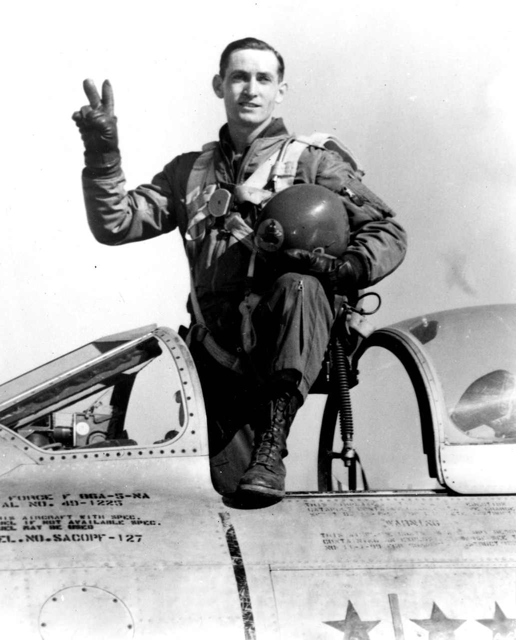 "A pilot stands in the cockpit of a plane with one leg propped on the side of it. He holds his helmet in one hand while forming a ""V for Victory"" sign with the fingers of his other hand."