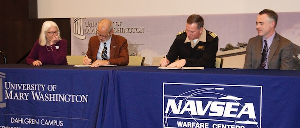 "IMAGE: KING GEORGE, Va. (Jan. 31, 2020) – Dr. Troy Paino, University of Mary Washington president, and Capt. Casey Plew, NSWCDD commanding officer, sign a Memorandum of Understanding (MOU) at a ceremony held at the UMW Dahlgren campus, Jan. 31. Looking on are Dr. Nina Mikhalevsky, the university's provost, and Darren Barnes, NSWCDD acting technical director, who were also MOU signatories. The MOU enables NSWCDD employees who qualify for the program to earn a project management certificate while applying the credits towards a Master of Business Administration. ""We are delighted about this opportunity and hold it up as a shining example of the partnerships we are pursuing,"" said Barnes. ""It would not be possible without the University of Mary Washington."" (U.S. Navy photo/Released)"