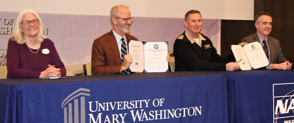 "IMAGE: KING GEORGE, Va. (Jan. 31, 2020) – Dr. Troy Paino, University of Mary Washington president, and Capt. Casey Plew, NSWCDD commanding officer, hold the Memorandum of Understanding (MOU) they signed at a ceremony held at the UMW Dahlgren campus, Jan. 31. Looking on are Dr. Nina Mikhalevsky, the university's provost, and Darren Barnes, NSWCDD acting technical director, who also signed the MOU which enables NSWCDD employees who qualify for the program to earn a project management certificate while applying the credits towards a Master of Business Administration. ""We are excited at the University of Mary Washington about this partnership and program,"" said Paino. ""This program really aligns with our mission and vision moving forward. Partnerships matter and we're here as a bridge to serve our community, our commonwealth, country, and the mission at Dahlgren."" (U.S. Navy photo/Released)"