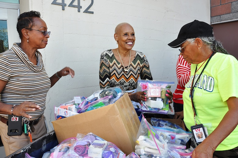 From left to right, Stephanie Hall, senior environmental protection specialist, Transportation and Special Projects Branch, U.S. Army Corps of Engineers Los Angeles District; Shirley Craig, donations and inventory associate at the Downtown Women's Center, Los Angeles; and Pauline Williams, parking attendant at the women's center, smile as they sort through plastic bags full of toiletry items donated Jan. 23 to the center by the U.S. Army Corps of Engineers Los Angeles District.