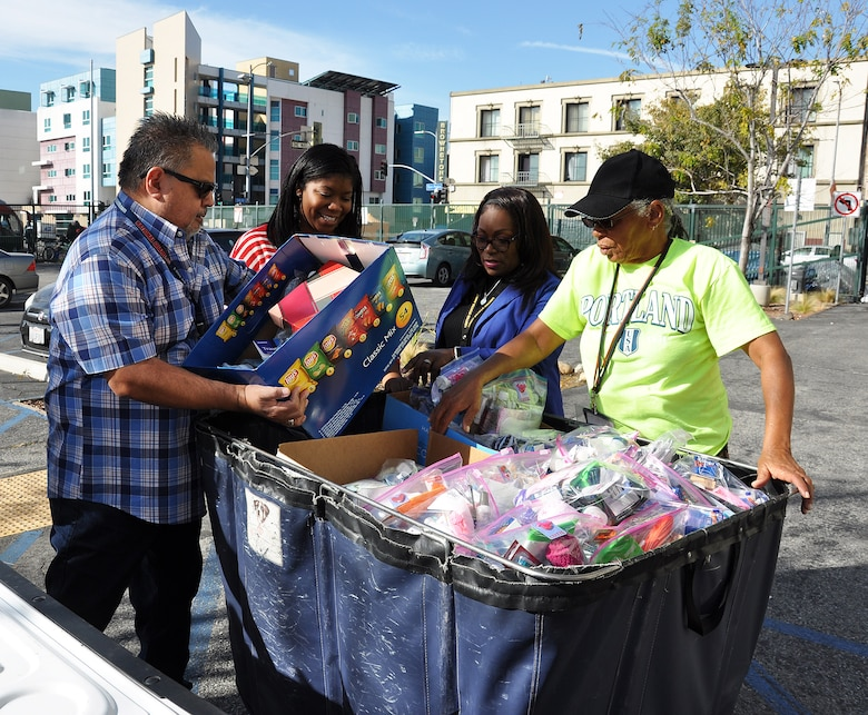 From left to right, Gerry Salas, environmental engineer; Arnecia Williams, regional value officer, Engineering Division; Felicia Weaver, administrative assistant, Public Affairs, all with the U.S. Army Corps of Engineers Los Angeles District, and Pauline Williams, parking attendant at the Downtown Women's Center, Los Angeles, unload boxes of toiletries into a large cart Jan. 23 at the women's center in Los Angeles.
