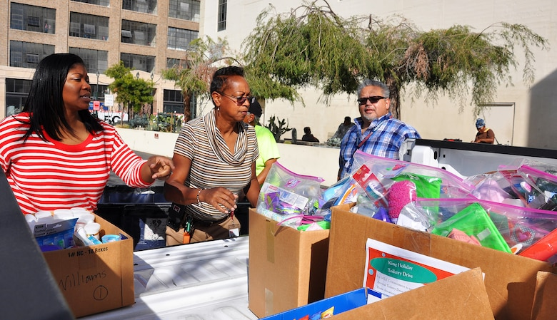 From left to right, Arnecia Williams, regional value officer, Engineering Division; Stephanie Hall, senior environmental protection specialist, Transportation and Special Projects Branch; and Gerry Salas, environmental engineer, all with the U.S. Army Corps of Engineers Los Angeles District, unload boxes of toiletries Jan. 23 at the Downtown Women's Center, Los Angeles.