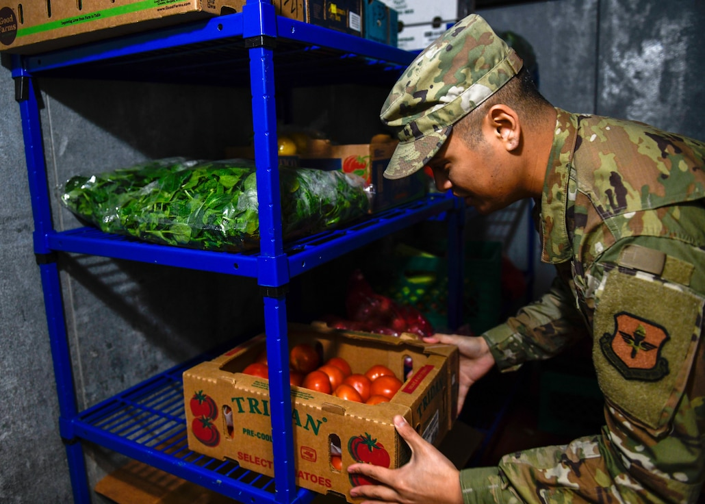 Staff Sgt. Joseph Deguino, 56th Operational Medicine Readiness Squadron Public Health communicable disease noncommissioned officer in charge, examines tomatoes during a monthly inspection Jan. 27, 2020, in Club 5/6 at Luke Air Force Base, Ariz. Every restaurant and food store on base, checking for discrepancies and ensuring that staff use mandated gear. Public health helps keep Airmen healthy, ready to train and deploy by inspecting facilities for food quality, performing audiograms and more. (U.S. Air Force photo by Airman 1st Class by Brooke Moeder)