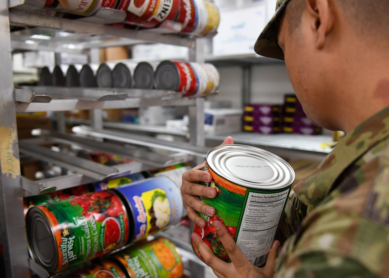 Staff Sgt. Joseph Deguino, 56th Operational Medicine Readiness Squadron Public Health communicable disease noncommissioned officer in charge, checks the expiration date on a canned good during a monthly inspection Jan. 27, 2020, in Club 5/6 at Luke Air Force Base, Ariz. While inspecting facilities, Deguino looks for expiration dates and ensures the food is properly covered. Public health helps keep Airmen healthy, ready to train and deploy by inspecting facilities for food quality, performing audiograms and more. (U.S. Air Force photo by Airman 1st Class by Brooke Moeder)