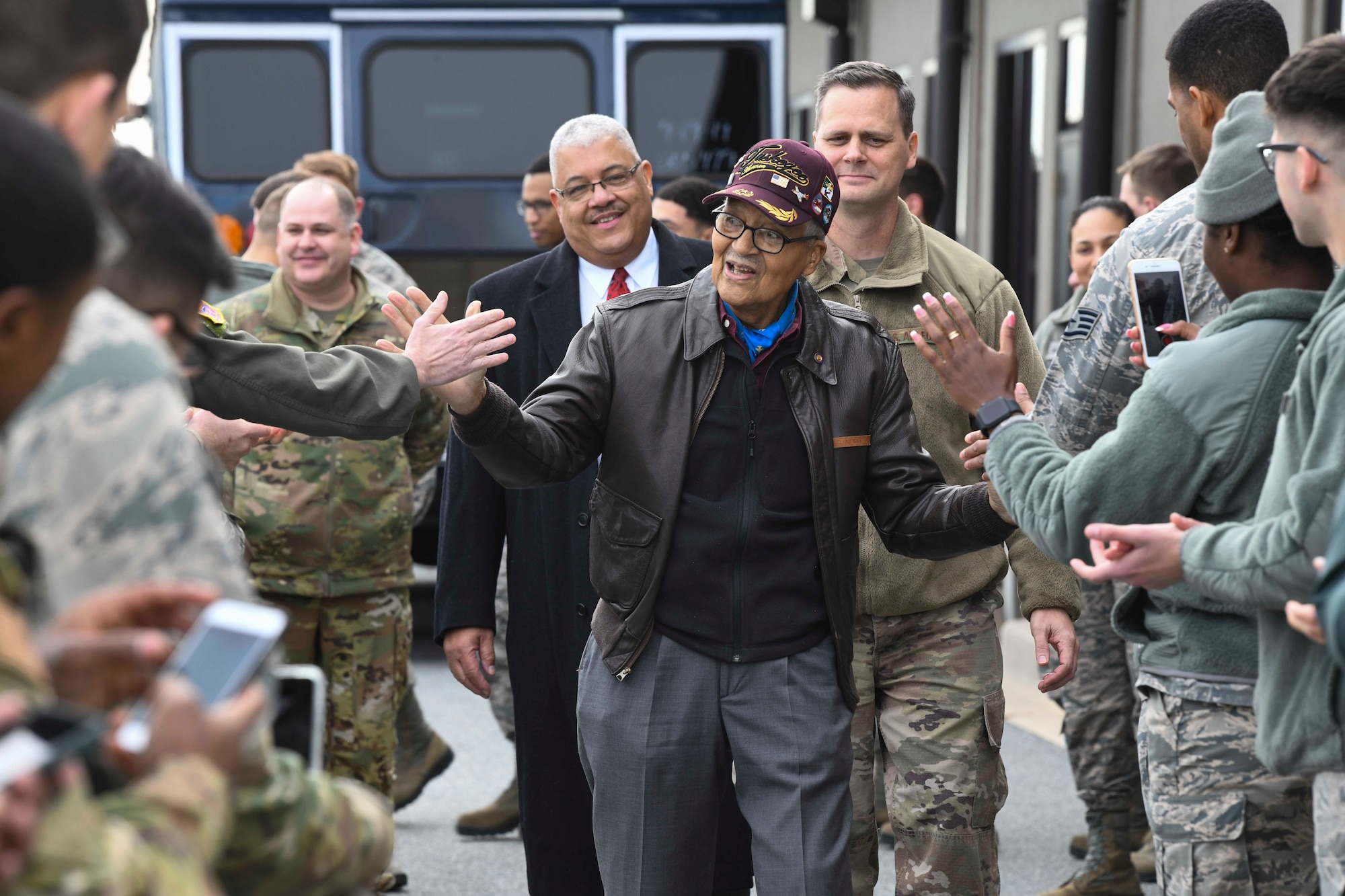 Retired Col. Charles McGee, one of the Tuskegee Airmen, high-fives Airmen during his visit Dec. 6, 2019, at Dover Air Force Base, Del. McGee served a total of 30 years in the U.S. Air Force, beginning with the U.S. Army Air Corps, and flew a total of 409 combat missions in World War II, the Korean War and the Vietnam War. The Tuskegee Airmen were the first African-American military aviators in the U.S. Army Air Corps. (U.S. Air Force photo by Senior Airman Christopher Quail)
