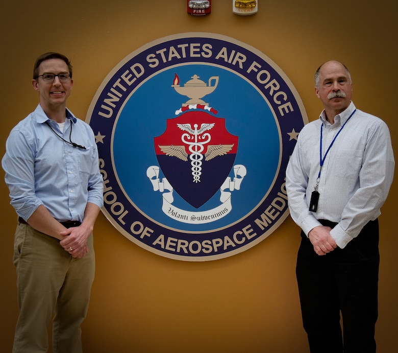 """Dr. Anthony Fries, a bioinformatics scientist, (left), and Dr. Paul Sjoberg, a program manager with the Department of Defense Global Respiratory Pathogen Surveillance Program at USAFSAM's Epi Lab, discuss how the lab and the Centers for Disease Control and Prevention monitor influenza to provide the U.S. Food and Drug Administration critical data for manufacturers of the flu vaccine in Episode 21 of AFRL's """"Lab Life"""" podcast, now available for download. (U.S. Air Force photo/Keith Lewis)"""