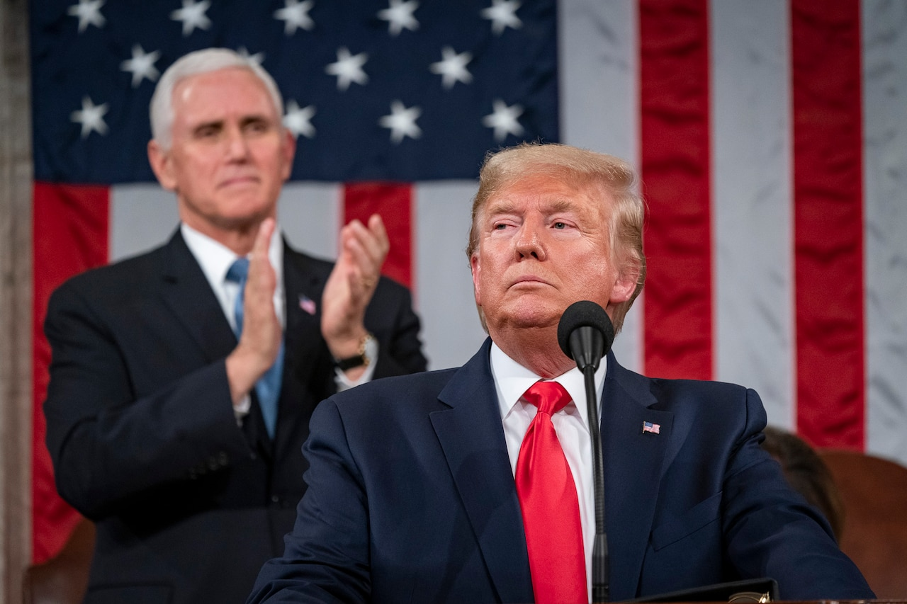 President Trump pauses during speech, with vice president standing and applauding in background.