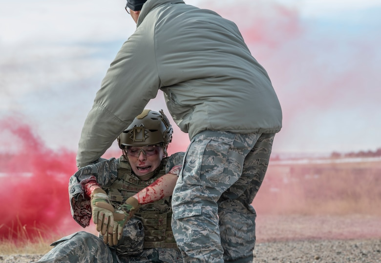 An Airman, reprresenting the injured, has been pulled out of a buring humvee and is placed away from danger for assessment during a 90th Civil Engineer Squadron Explosive Ordinance Disposal flight Self Aid Buddy Care training Jan. 16, 2020. The one-day training allowed Airmen from the 90th Mission Support Group to enhance their knowledge on Self Aid Buddy Care, in a combat environment, including treatment for a collapsed lung. (U.S. Air Force photo by Senior Airman Abbigayle Williams)