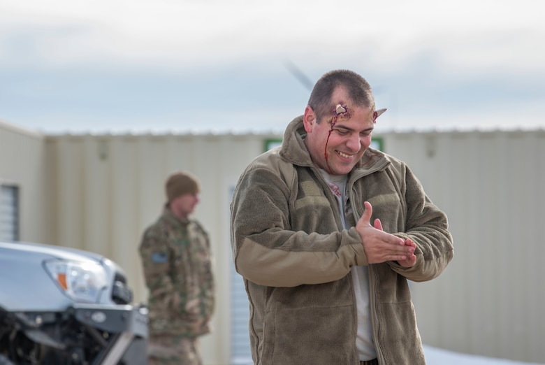An Airman, playing injured, walks away after receiving mock Self Aid Buddy Care during the 90th Civil Engineer Squadron Explosive Ordinance Disposal flight training Jan. 16, 2020, at F.E. Warren Air Force Base, Wyo. A majority of the Airmen have varying injuries for the responding team to diagnose and treat, under a mock combat situation. (U.S. Air Force photo by Senior Airman Abbigayle Williams)