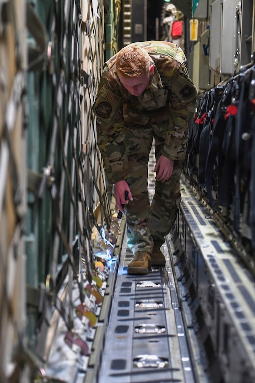 Airman 1st Class Kam Watt, 4th Airlift Squadron loadmaster, double checks the secure netting of pallets of cargo aboard a C-17 Globemaster III as part of the pre-flight checklist before taking off from Spangdahlem Air Base, Germany, Dec. 18, 2019. Loadmasters are responsible for ensuring the security of cargo and proper weight distribution. (U.S. Air Force photo by Airman 1st Class Mikayla Heineck)