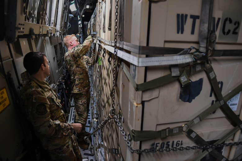 Master Sgt. Andrew Reilly, 4th Airlift Squadron loadmaster, observes Airman 1st Class Kam Watt, 4th Airlift Squadron loadmaster, attach and tighten an additional strap onto a piece of cargo aboard a C-17 Globemaster III before taking off from Spangdahlem Air Base, Germany, Dec. 18, 2019. The metal piece at the end of an existing strap had started to deteriorate, so as an added security measure the loadmasters attached one of their straps. (U.S. Air Force photo by Airman 1st Class Mikayla Heineck)