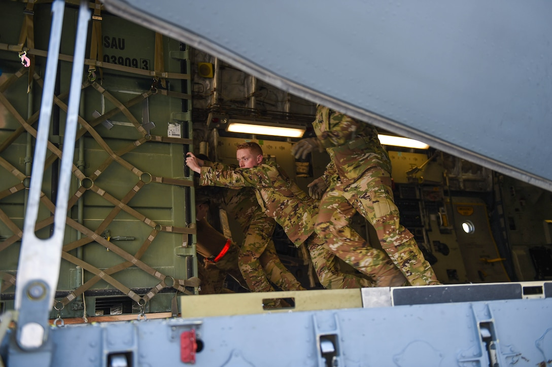 Airman 1st Class Kam Watt, 4th Airlift Squadron loadmaster, off-loads a piece of cargo off of a C-17 Globemaster III onto a K-loader in Kuwait, Dec. 18, 2019. The aircraft has multi-directional rollers towards the back of the cargo bay that make it easier to push and maneuver cargo. (U.S. Air Force photo by Airman 1st Class Mikayla Heineck)