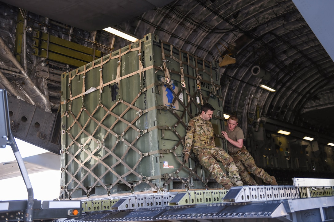 Master Sgt. Andrew Reilly and Airman 1st Class Kam Watt, 4th Airlift Squadron loadmasters, offload a piece of cargo from a C-17 Globemaster III in Kuwait, Dec. 18, 2019. The C-17 is eqipped with multi-directional rollers in the floor to aid in the on and off-load of cargo. (U.S. Air Force photo by Airman 1st Class Mikayla Heineck)