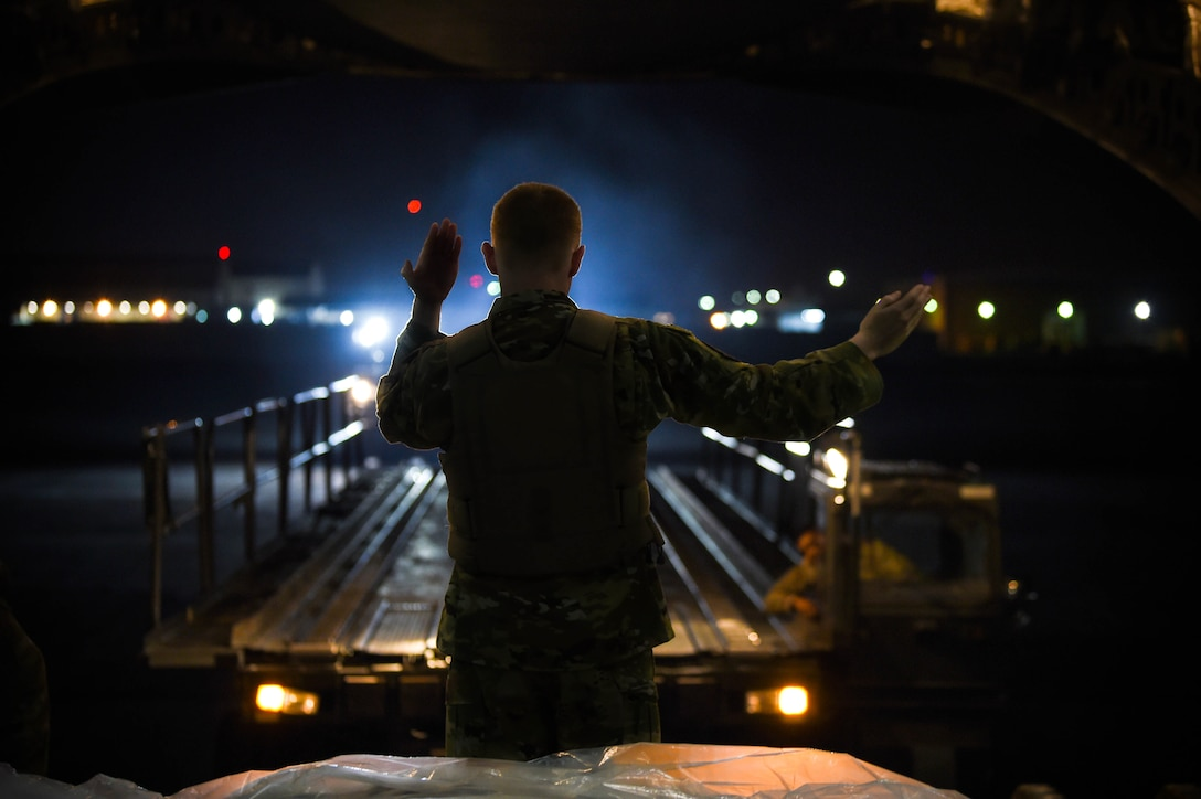 Airman 1st Class Kam Watt, 4th Airlft Squadron loadmaster, marshalls a K-loader up to the back of a C-17 Globemaster III to offload cargo in Iraq, Dec. 20, 2019. A C-17 loadmaster is responsible for the on-load and off-load of cargo from the aircraft, and for securing it while in transit. (U.S. Air Force photo by Airman 1st Class Mikayla Heineck)