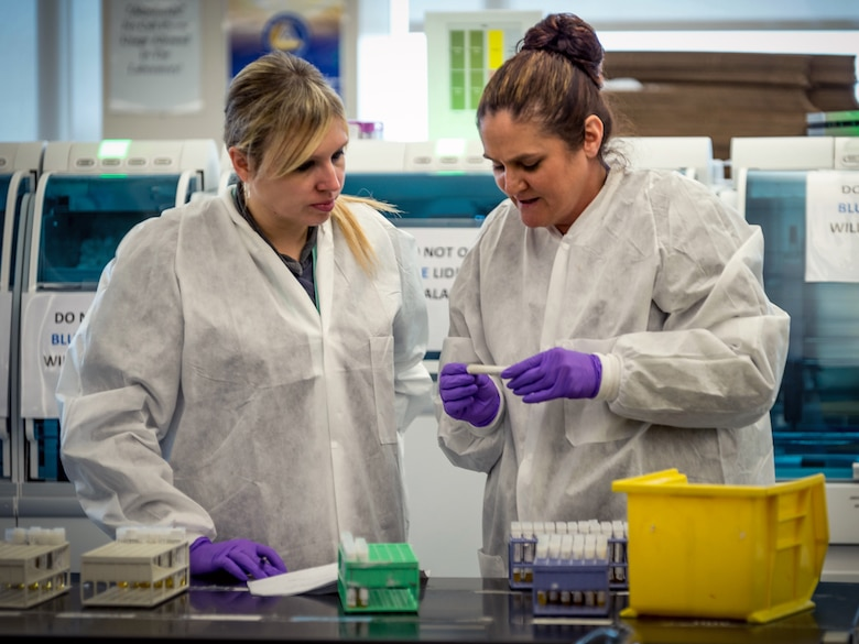 Lindsey White and Tiffany Miracle prepare serology samples to load into an automated analysis system in the immunodiagnostic section of the Epidemiology Laboratory Service, also known as the 'Epi Lab,' at the 711th Human Performance Wing's United States Air Force School of Aerospace Medicine and Public Health at Wright Patterson AFB, Ohio, Jan. 30, 2018. (U.S. Air Force photo by J.M. Eddins Jr.)