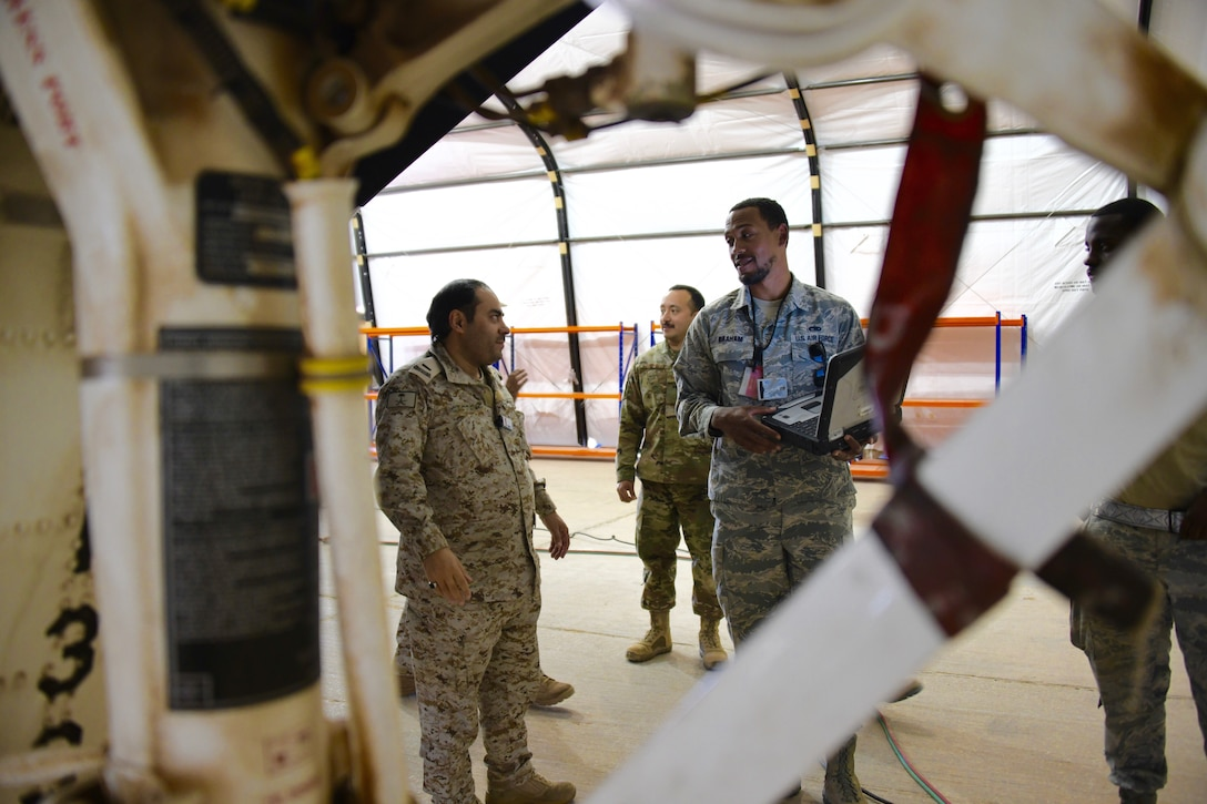 U.S. Air Force Tech. Sgt. Chris Graham (right), 378th Expeditionary Maintenance Squadron nondestructive inspection noncommissioned officer in charge, talks to Royal Saudi Air Force Chief Salman D. Al-Malki , PSAB head of aircraft maintenance inspections, about the processes of inspecting an F-15E Strike Eagle at Prince Sultan Air Base, Kingdom of Saudi Arabia, Feb. 4, 2020.