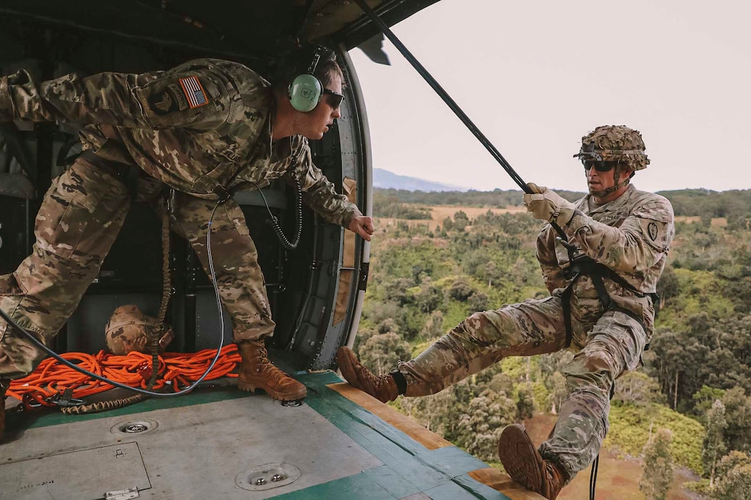 A soldier hangs off the side of a helicopter door while another soldier looks in his direction.