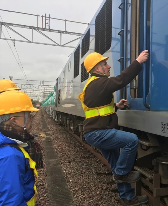 Maj. Justin D'Agostino,logistics readiness officer who currently serves as the commander of Defense Logistics Agency Energy Japan based at Yokota Air Base, Japan, climbs onto a train before it transports fuel to a defense fuel support point. (Courtesy photo)